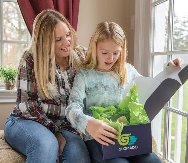 Mother and daughter opening GLOMADO box